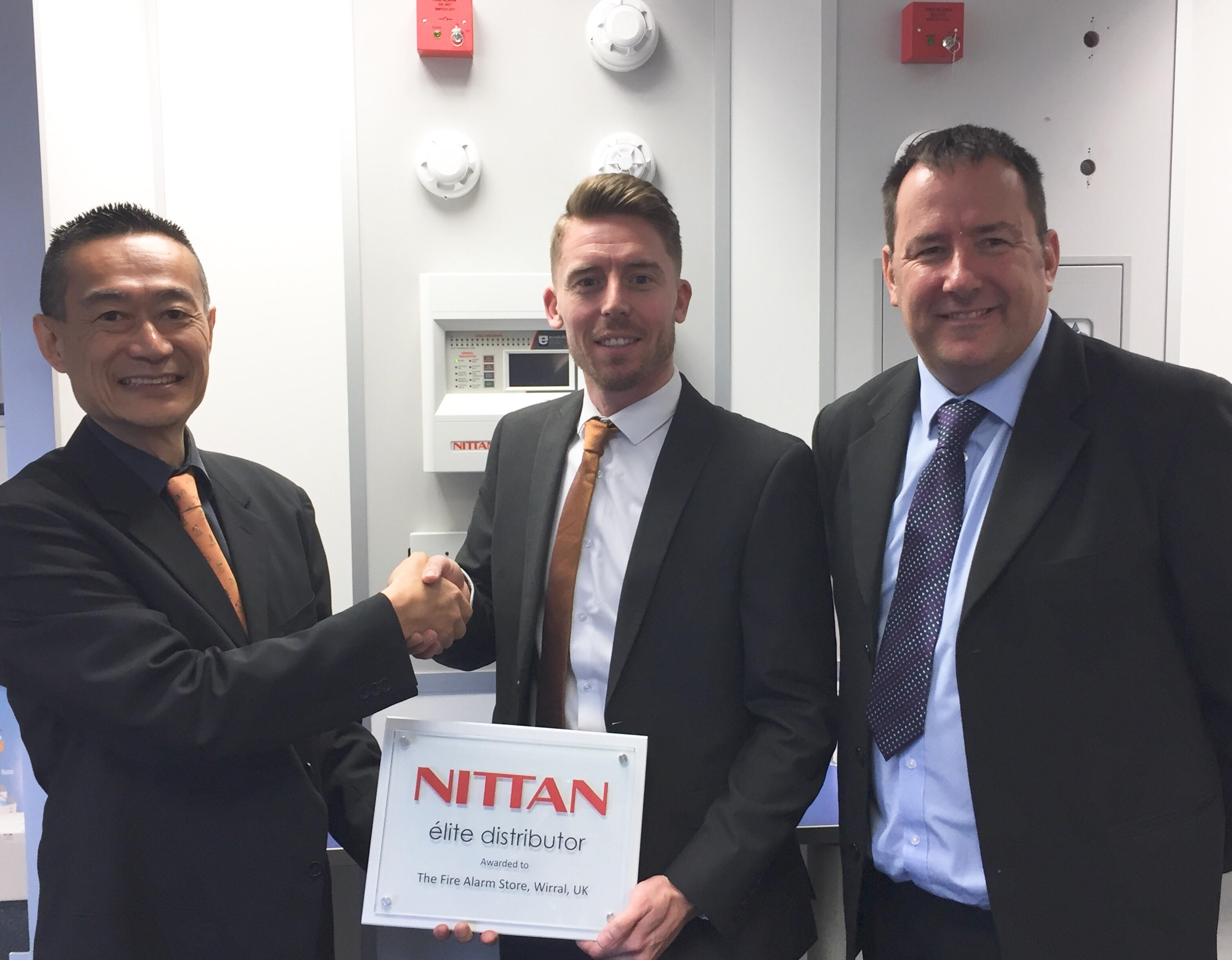 Nittan MD, Mr Kadokura presenting the plaque to Alan Fowlie of the Fire Alarm Store, with Nittan RSM, Barry Simpson, on the Right hand side